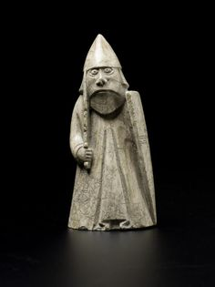 Chessman or chess piece, warder or rook, wearing an aketon with sword, shield and helmet, standing, of sperm whale tooth, found in an underground chamber in the parish of Uig, Lewis in 1831: Scandinavian, late 12th century