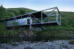 To minimize disruption to the hillside vineyard, the Flood Plain House sits on the banks of the Potlatch River. The home is elevated 12 feet off the ground by four concrete pillars in order to avoid flooding and visits from the native rattlesnakes. A scaffolding made from steel trusses frame the Galvalume metal exterior and expands out to create a cantilever deck over the water, while a second extension runs south to house a wing for the bedrooms.