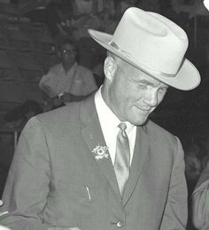 ❦ (4 July 1962)  Mercury astronaut John H. Glenn Jr., wearing a new cowboy hat and a badge in the shape of a star, leafs through his program as he is served his food at the Sam Houston Coliseum. A large crowd was on hand to welcome the Mercury astronauts to Houston, Texas.