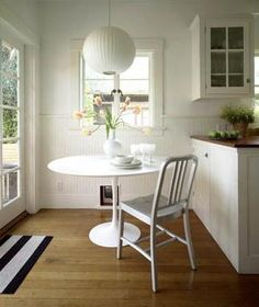 Wood, stripes, a touch of metal and saarinen -- that's how to do it. #white #kitchen