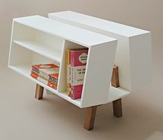 Penguin Donkey II - Ernest Races seminal 1963 update of the original 1939 Penguin Donkey. Designed, as its name suggests, to hold the original paperbacks, with a central slot for magazines and a flat top to allow use as a side table. Made of white lacquered wood with solid cherry wood legs.