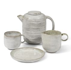 Dame Lucie Rie 1902-1995 AN EARLY TEA SET (COMPRISING OF A TEAPOT, JUG, CUP AND SAUCER) each signed with Artist's initials, earthenware with a white glaze, tallest: 11cm. Executed circa 1930.