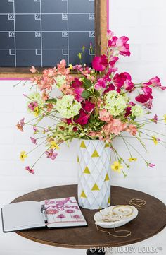 Create a modern marvel by painting the triangular shapes on a white, geometric vase with acrylic paint. Once your masterpiece is dry, pop in fresh or faux floral stems for the finishing touch!