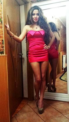 ATTRACTIVE BRUNETTE LEGGY IN SHORT GOWN------HEELS----LONG CURLY HAIR----HIPS IN MIRROR-----GOLD NECKLACE AND BRACELET