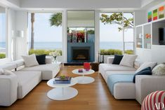 B&B Italia sofas are grouped with Cappellini tables in the living room of designer Abigail Turin's California beach house; the floor lamp is by Flos, the throw is by Hermès, and the walls are painted in Benjamin Moore's Chantilly Lace.