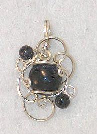 The mini sculpture.  A 10mm cabochon (a stone with a flat back and domed top, many colors to choose from) in delicate swirls of sterling or 14kt gf wire, with 4mm accent beads.  $18 - $20 depending on the stone.  At www.wiregems.com