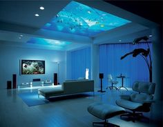 a huge well arranged living room. room is set up with cooling and crazy feel by the aquarium unified to its ceiling. room is all with pastel shades and the color reflection is due to aqua setup with a transparent glass to roof.