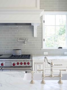 Light Grey Subway Tiles with white grout, pot-filler tap, Wolf range, Carrara marble counters, white cabinets