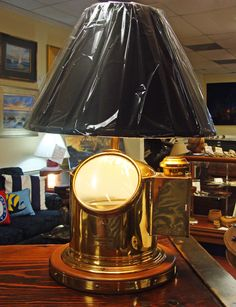 A handsome vintage brass life boat binnacle that was re-purposed into a nautical table lamp many years ago. The solid brass helmet shaped binnacle that houses a gimbaled Coubrot & Scrutton, Ltd, London compass, survives in working order.