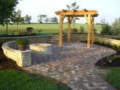 Pergola with paver patio, small retaining walls, and fire pit. #TopekaLandscape
