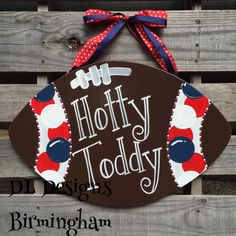 Wood football door hanger in red, blue, and white with Hotty Toddy written on the front. The polka dot ribbon is securely attached on the