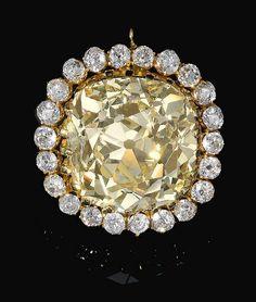 FANCY YELLOW DIAMOND AND DIAMOND JEWEL, LATE 19TH CENTURY  Estimate:1,310,000 – 1,680,000 CHF The cushion shaped fancy yellow diamond weighing 74.53 carats, set within a border of similarly shaped diamonds.