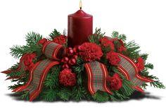 Celebração da família com este arranjo para o centro da mesa. Uma incandescência de 15 cm com uma vela, fita de tafetá e mini enfeites de Natal com folhagens sazonais de tuia, pinheiro branco, abeto de Douglas e cravos vermelhos.  Fotografia: Teleflora.com.