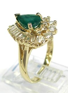Ladies 14kt yellow gold emerald and diamond ring. Ring has 1 pear shape genuine emerald gemstone weighing .92ct. Also set in ring are 10 baguette cut diamonds and 18 brilliant round cut diamonds weighing a total of  1ct.