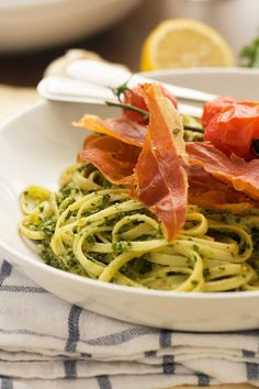 Homemade pesto made with healthy kale and walnuts - stirred into linguine and all topped with delicious roasted tomatoes and crispy prosciutto. Mmmm.