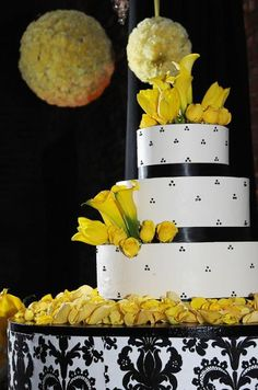 This black and white wedding cake with yellow flowers matches the wedding color theme.