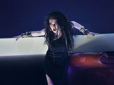 Frau mit schwarzen Haaren und schwarzem Kleid hält sich an Balken fest