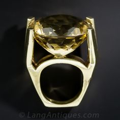 A very chic and crisply architectural 14k yellow gold cocktail ring (lots of cocktails!) from the late 1960s-early 70s, featuring an enormous 46 carat round faceted Citrine emitting a golden sunshiny glow. The mounting features sleek flying V shoulders and a smooth geometric ring shank. A grand and glorious 1960s high-moderne statement, in a finger size 6 3/4. Measures 1 inch(+) across.