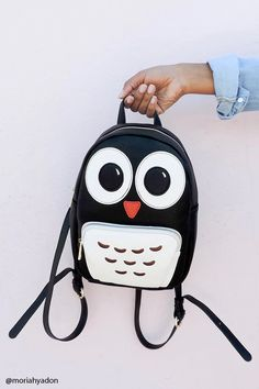 A structured mini faux leather backpack featuring an owl with large eyes, top handle, zip-up top, adjustable shoulder straps, a front contrast zippered pocket, and two interior slip pockets.