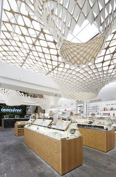 within the innisfree store in seoul, SOFTlab has suspended an undulating spatial installation that weaves its way through through the luminous retail space.
