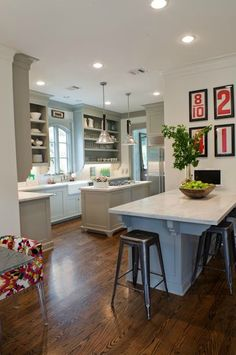 pale dove gray kitchen cabinets, white carrera marble counter tops, love the red/black/white framed graphic art.