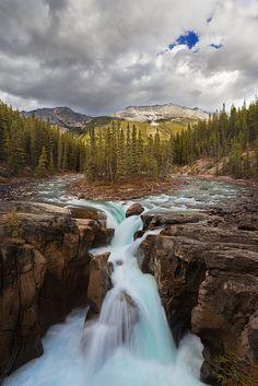"""The Sunwapta River cascades over Upper Sunwapta Falls in Jasper National Park on a stormy afternoon. Alberta, Canada."""