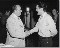 Elvis shakes hands with Colonel Parker, Friday January 6th 1961 - on set Birthday celebrations for Elvis 26th Birthday. Lamar Fike is on the left of frame and Sonny West on the right of frame..(inside Wild in the country)