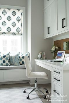 chic first floor home office features floor to ceiling white built in shelves cabinets and drawers illuminated by a white frosted glass jar lanter chic home office features