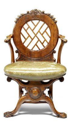 A George II walnut open armchair The leaf-carved and crocketed cresting above a panel of pierced 'Chinese' paling, the open arms above a nailed leather seat, on X-frame front supports joined by turned stretchers and with front paw Bonhams
