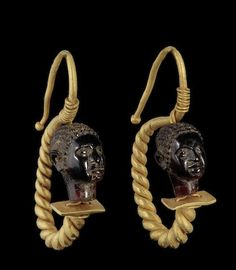 A pair of Roman gold and garnet African head earrings, Circa 1st-2nd Century C.E. Each composed of a finely carved garnet bead in the form of an African head with short incised hair, strung with double gold wire connected above and below to a tapering thick loop of twisted wire, the ear hook curving back on itself to form an s-shape, 1¾in (3.5cm) long including hook (2).