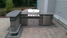 Outdoor kitchen on paver patio with built in fridge and bar.
