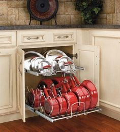 You can buy pull out cabinet organizers that will hold your cookware and keep it neatly in place. They work about like the drawers in your dishwasher.