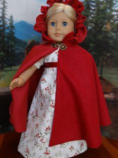 Ivory and red holiday regency gown and red cloak  by ValorieoftheDolls on Etsy. Made from the 1790 Open Pelisse and Regency Dress and the Irish Kinsale Cloak patterns. Find them at the http://www.pixiefaire.com/collections/thimbles-and-acorns/products/1790-open-pelisse-and-regency-dress-18-doll-clothes. http://www.pixiefaire.com/collections/thimbles-and-acorns/products/irish-kinsale-cloak-18-doll-clothes. #pixiefaire #1790openpelisseandregencydress #irishkinsalecloak