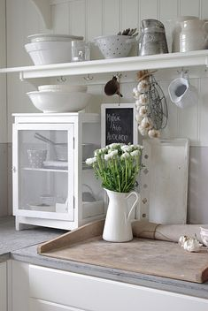 Check out that cute chalkboard to use for reminders or grocery needs in this immaculate white kitchen.