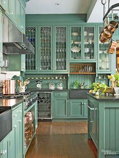 Gorgeous soft teal, grey and copper kitchen - love the hanging copper pots and glass fronted upper cabinets.