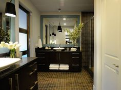Brown tile floors add warmth to this spacious master bathroom, found in HGTV Green Home Dark wood vanities and large blue-framed mirrors create two separate vanity areas, each dressed with a different floral arrangement. Blue Brown Bathroom, Brown Bathroom Decor, Bathroom Ideas, Green Bathrooms, Bathroom Trends, Bathroom Inspiration, Minimalist Bathroom Furniture, Modern Furniture, Houses