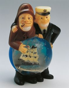 Close-up of figurines of sailors with a snow globe