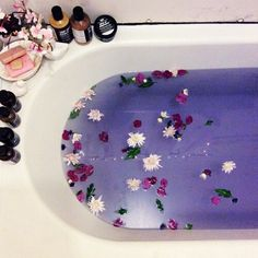 Bathtub with floating Flowers & petals in purple water