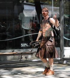 https://flic.kr/p/8yfoq3 | I see you too, Mod Scot Shaman, headscarf, glasses, beard, skateboard, utility kilt, belt, tatoos, piercing, pack, (Tatoos include fiery Totemic Owl, octopus, dog, and Salvador Dali's Face) Downtown Vancouver BC, Canada
