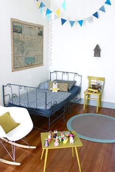 Boys vintage room. Wooden floor, white walls. Green and blue contrasts. French inspired vintage bed. Old map on wall.