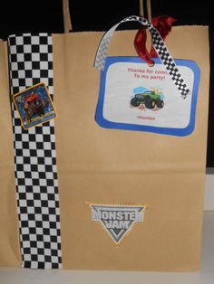 Monster Jam Bday Party Giftbag  I found something similar to this here on Pinterest but I changed it up some. I found all materials at our local Michaels store with the exception of the MJ stickers.  Stuff you'd need for this project is:  *Checkered tape *Monster Jam stickers (ordered from birthday express) *Blue construction paper *Brown bag *Red ribbon *Checkered ribbon *Hole puncher *Printer Paper