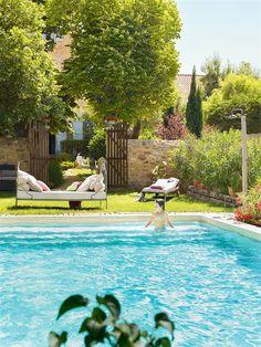 Jardín con piscina y niño bañándose