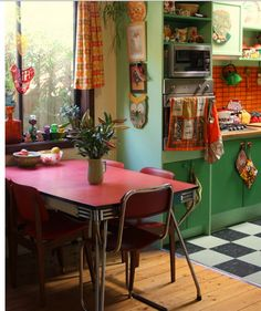 Kitchen! Red vintage table. Black/white checked floor. Green cabinets/orange tiles.