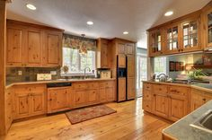 Rustic Kitchen with Raised panel, DuraSupreme Mullion Pattern #1, Slate Tile, Complex granite counters, Inset cabinets