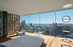 狭小住宅の3階のガラス張りの開放的なベッドルーム