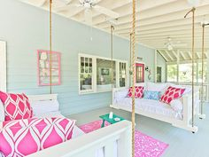 Fun bright pink and light blue front porch swings