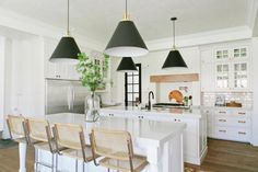 This transitional white kitchen from Kristen Krason and Erin Morgan features classic cabinetry and subway tile blended with contemporary elements such as the striking black cone pendant lights above the polished white countertops.