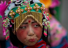 A Chinese child dressed in a traditional costume prepares for her performance ahead of the Duanwu Festival opening ceremony held at Shunyi Olympic Rowing-Canoeing Park in Beijing, China Friday, June 22, 2012. The Duanwu festival, also known as Dragon Boat festival, which falls on the fifth day of the fifth month of the Chinese calendar, commemorates the death of Qu Yuan, a famous Chinese poet from the kingdom of Chu who lived during the Warring States period. (AP Photo/Andy Wong)