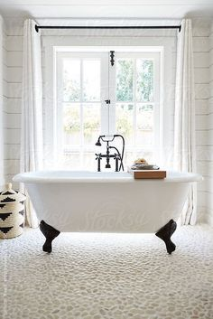 Rustic modern farmhouse bathroom in small cottage with clawfoot tub, white oak vanity, and white pebble stone floor
