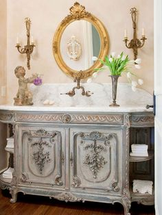 Love the painted French vanity sink, gold mirror, & sconces!